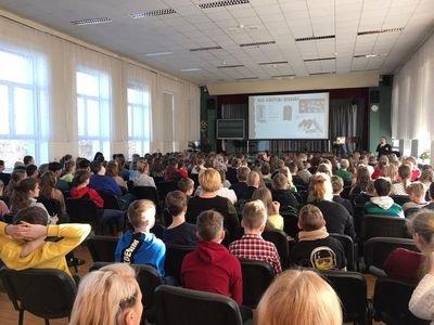 Skolas aktu zālē sēž bērni un skatās prezentāciju