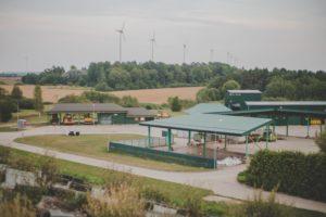 Poligona Ķīvītes šķiroto atkritumu novietne ar zaļu jumtu. Tālumā poligona apkārtne un koki.