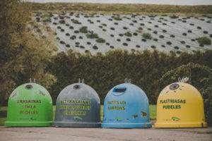 Attēlā redzami četri šķiroto atkritumu konteineri, no kreisās- zaļš, pelēks, zils, dzeltens.